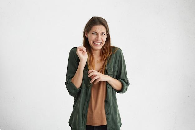 嫌悪感、嫌悪感、嫌悪感を表現するカジュアルな服装のブルネットの女性は、顔をしかめ顔の緊張感を無視します。
