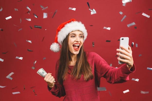 크리스마스 모자 돈을 들고 selfie 개념에 갈색 머리 여자