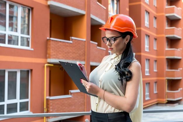 Брюнетка женщина в шлеме, делая заметки на строительной площадке