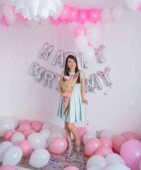 튤립 꽃다발을 들고 민트 드레스에 갈색 머리 여자. 흰색과 분홍색 풍선이 있는 생일 장식, 튤립 꽃다발, 흰색 벽에 파티를 위한 색종이 조각. 생일 기념일을 축하합니다.
