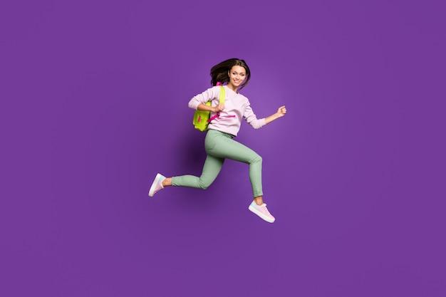 Брюнетка в пастельном свитере позирует у фиолетовой стены