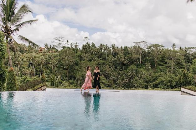 발리에서 친구와 손을 잡고 핑크 드레스에 갈색 머리 여자. 정글에 수영장 근처에 서있는 여성 모델의 야외 사진.