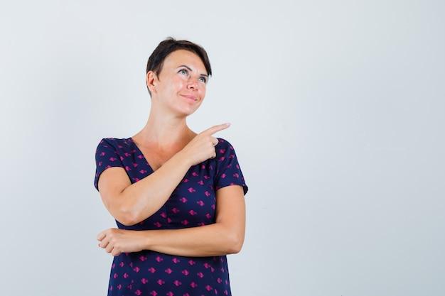 紫と赤の模様のドレスを着たブルネットの女性は、人差し指で右を指して、笑顔で楽観的な正面図を探しています。
