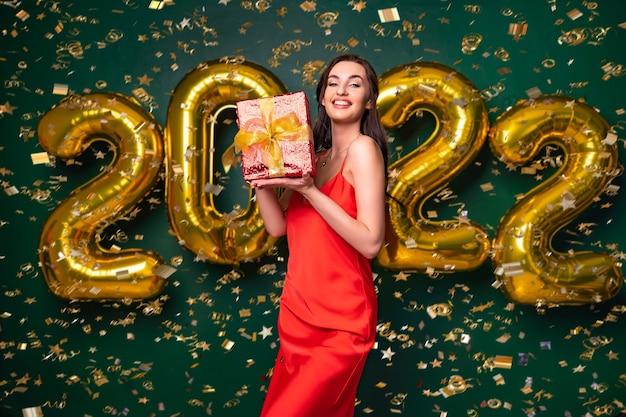 빨간 드레스를 입은 갈색 머리 여자는 황금 활 휴가 컨셉으로 선물 상자를 들고 있습니다.