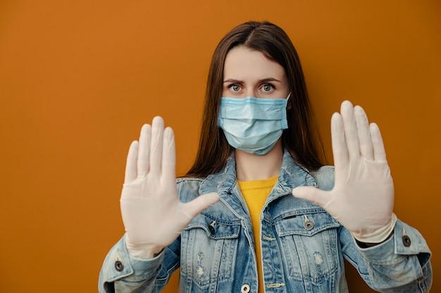 멸균 얼굴 마스크 장갑에 갈색 머리 여자, 중지 제스처에 카메라를 향해 손을 끌어, 한계를 보여줍니다, 갈색 벽에 고립 된 데님 재킷을 착용. 격리 유행성 코로나 바이러스 바이러스 개념