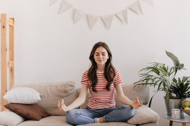 Брюнетка в полосатой футболке медитирует, сидя на диване в гостиной