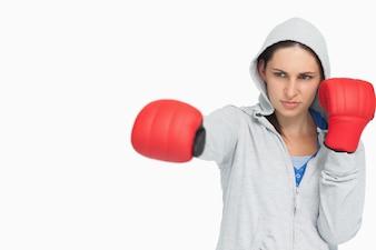 Brunette woman in sweatshirt boxing
