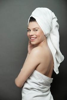 タオルとタオルでブルネットの女性はいたずらな笑顔でカメラに向けられました