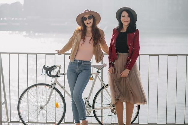 다리에 친구와 함께 서있는 빈티지 긴 치마에 갈색 머리 여자