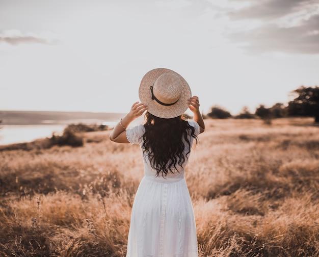 Брюнетка в белом платье и шляпе на закате