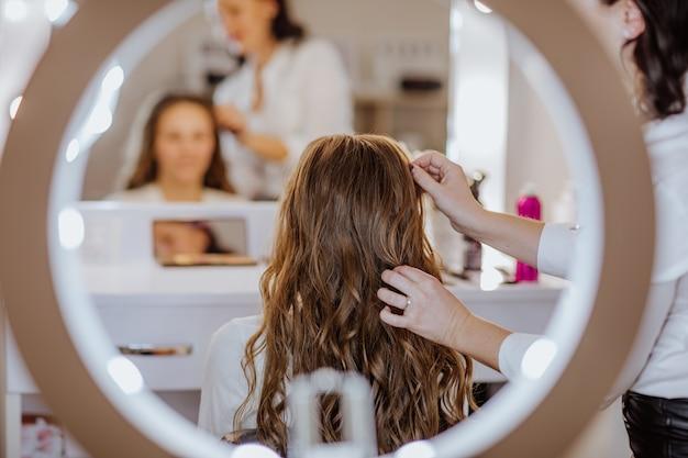 Брюнетка женщина в белой рубашке делает вьющиеся прически для подростковой красивой девушки с длинными волосами.