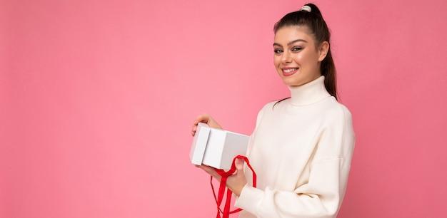 ギフトボックスを保持している白いセーターを着てピンクの背景の壁に分離されたブルネットの女性
