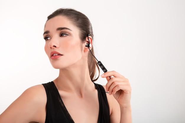 Brunette woman in jogging black top listening to music on earphones posing on grey