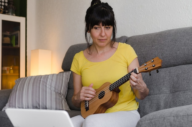 Brunette woman learning to play ukulele online, watching a class on her tablet