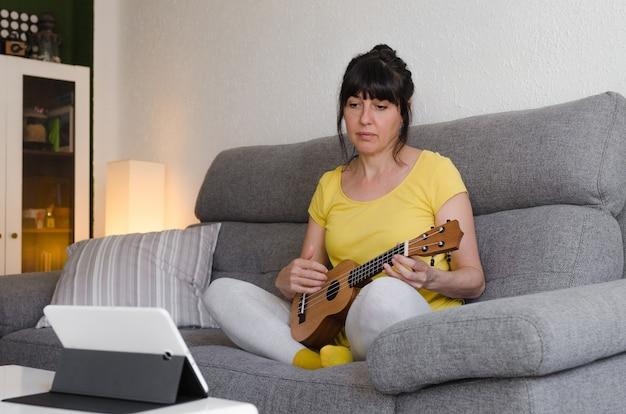 オンラインクラスでウクレレを演奏することを学ぶブルネットの女性