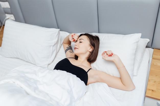 갈색 머리 여자는 아침에 침대에 누워 그녀의 팔과 몸을 스트레칭 일어나