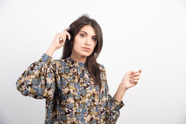 Donna castana che ascolta la musica con espressione seria.