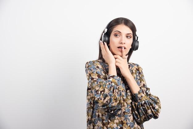 ヘッドフォンで音楽を聴いているブルネットの女性。
