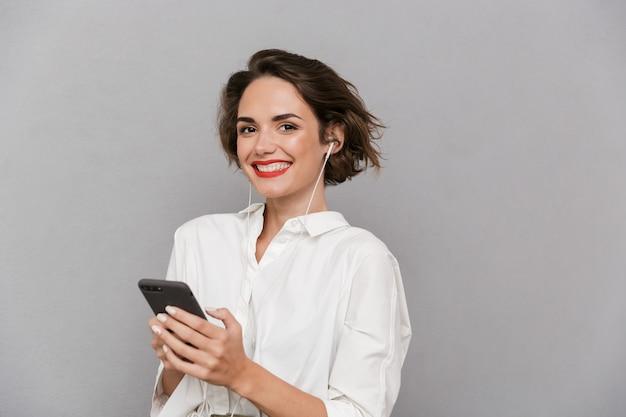 灰色の壁に隔離されたイヤホンを介してスマートフォンで音楽を聴いているブルネットの女性