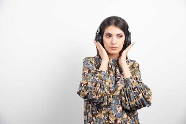 真剣な表情で音楽を聴いているブルネットの女性。