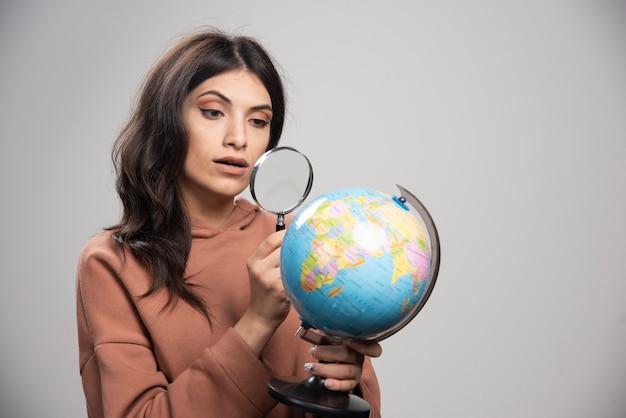 虫眼鏡で地球を見ているブルネットの女性