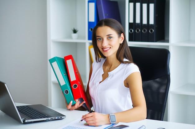 Брюнетка женщина смотрит на телефон во время работы