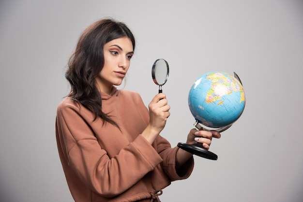 Donna castana che esamina globo con lente d'ingrandimento
