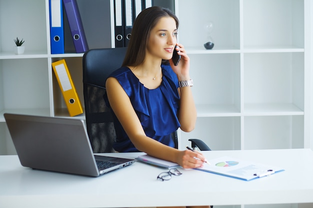Brunette woman looking at phone while working