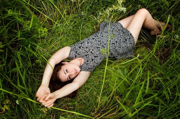 緑の草の上に横たわっているブルネットの女性