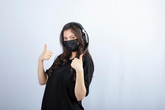 Brunette woman in medical mask listening music in headphones and showing thumbs up