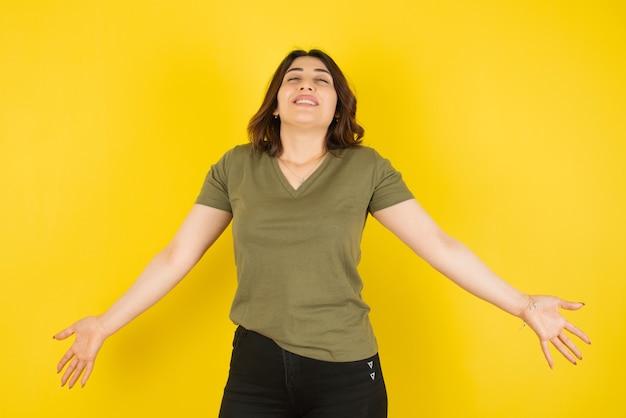 Modello di donna bruna in piedi e in posa contro il muro giallo