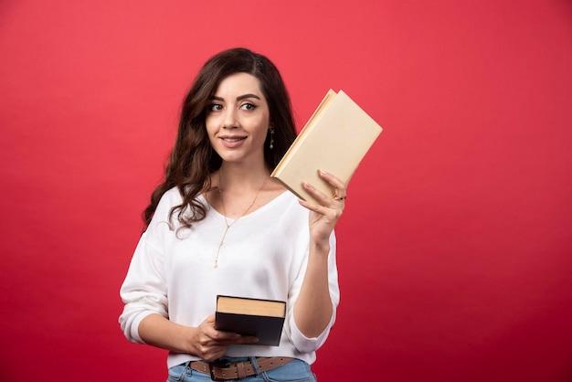 Брюнетка женщина предлагает книгу на красном фоне. фото высокого качества
