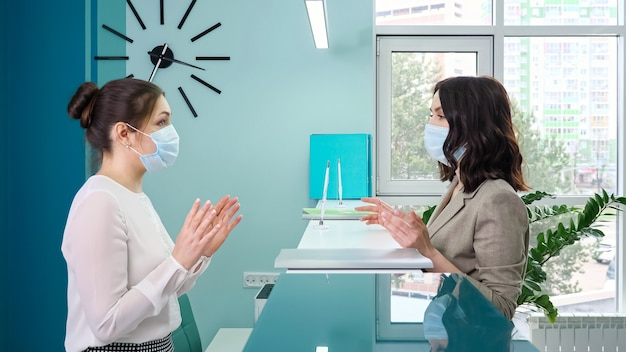 Brunette woman office manager with protective mask talks to lady patient standing at reception counter against window in hospital close side view