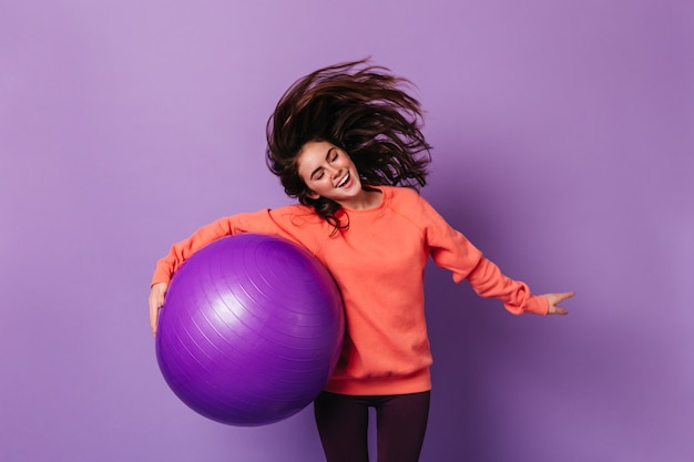Brunette woman in orange sweatshirt plays with hair and holds purple fitball on isolated wall