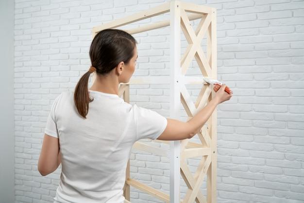 Брюнетка женщина рисует небольшую деревянную стойку в белый цвет