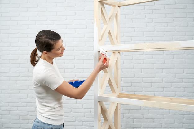 Brunette woman painting wooden rack in empty room