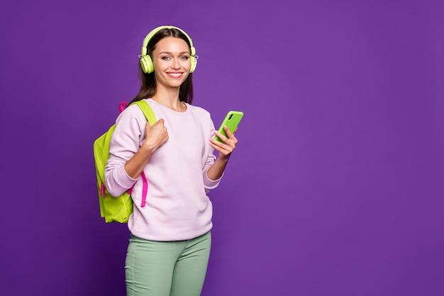 Brunette woman in pastel sweater posing against the purple wall