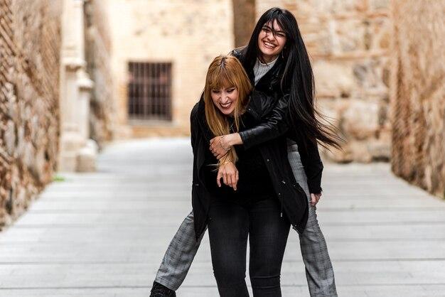 갈색 머리 여자는 금발의 여자에 편승. 도시 거리에서 즐거운 시간을 보내십시오. 우정과 행복의 개념.