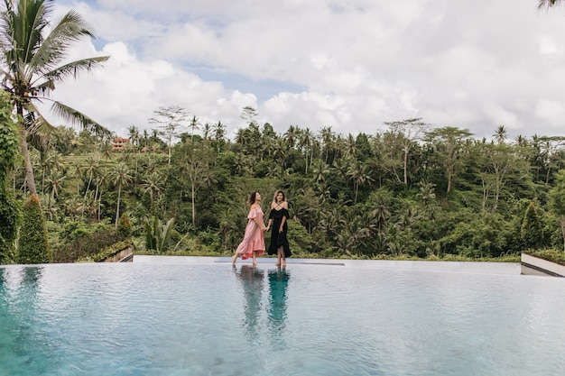 Brunette woman in pink dress holding hands with friend in bali. outdoor photo of female models standing near pool on jungle.
