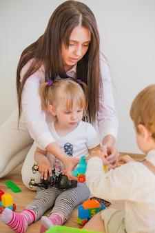 Брюнетка женщина играет с детьми