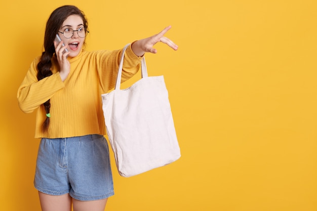 Brunette woman pointing index finger aside, showing cool thing with low price in mall