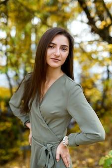 オリーブのドレスを着て秋の公園でブルネットの女性の肖像画