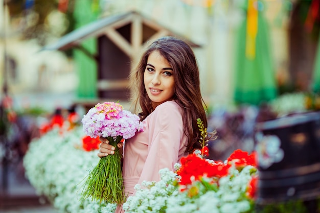 Brunette woman poses with pink bouquet among flowerpots