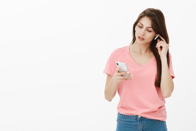 Брюнетка женщина позирует в студии со своим телефоном и наушниками