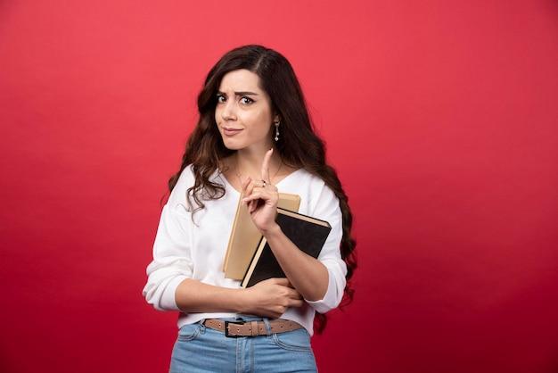 갈색 머리 여자는 빨간색 배경에 책과 함께 포즈입니다. 고품질 사진