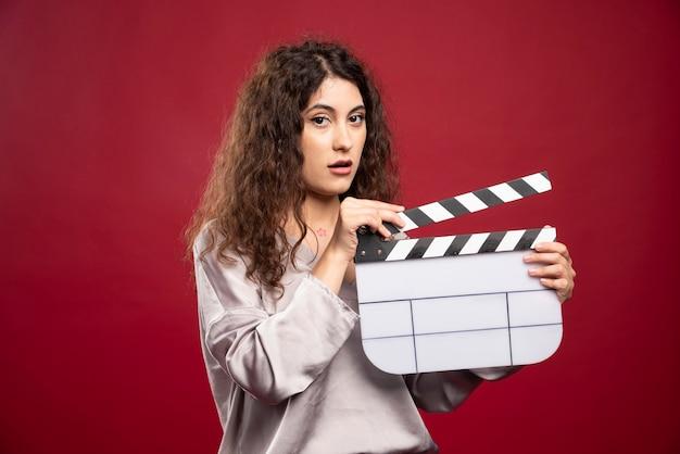 Clapperboard와 함께 포즈를 취하는 갈색 머리 여자.