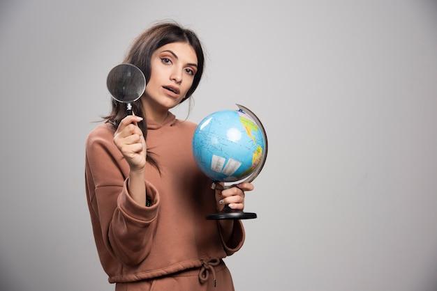 虫眼鏡と地球儀でポーズをとるブルネットの女性 無料写真