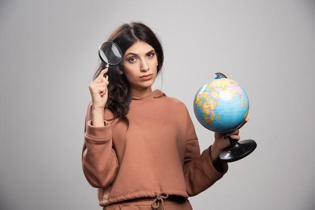 虫眼鏡と地球儀でポーズをとるブルネットの女性
