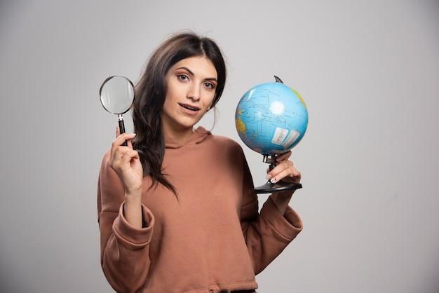 Donna castana che posa con la lente d'ingrandimento e il globo
