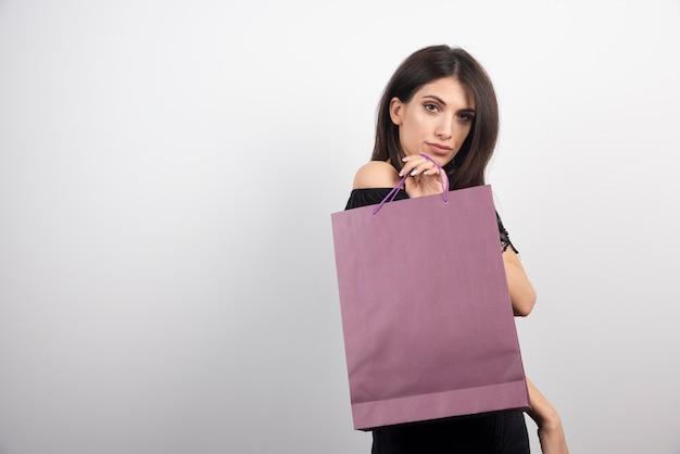 갈색 머리 여자 쇼핑 가방과 함께 포즈입니다.
